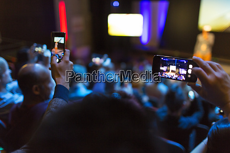 audience with smart phones videoing conference