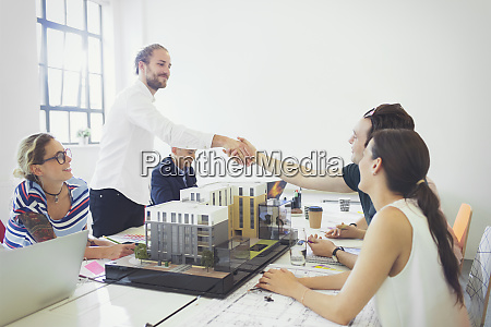 architects handshaking in conference room meeting