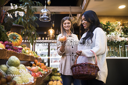 happy multi ethnic friends buying fruits