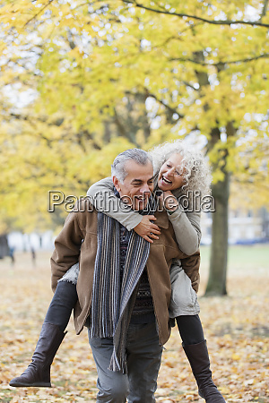 playful senior couple piggybacking in autumn
