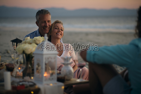 smiling mature couple looking at male
