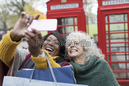 smiling senior women friends taking selfie