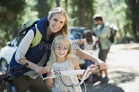 smiling mother and daughter with bicycle