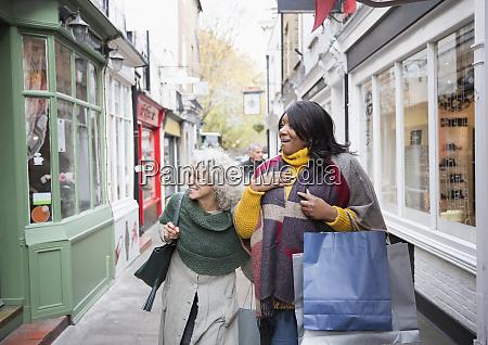 senior women friends window shopping outside