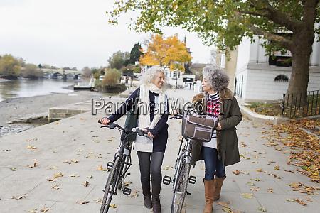 smiling active senior women walking bicycles