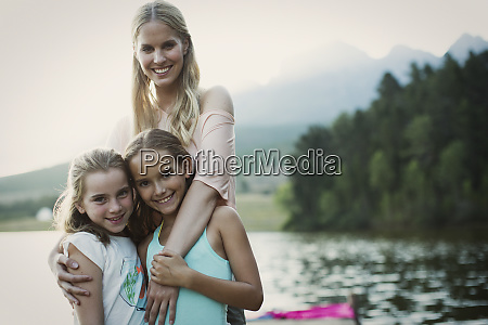mother and daughters smiling at lakeside
