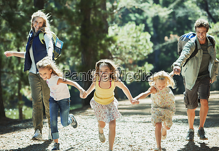 smiling family holding hands and running
