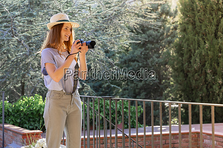 female photographer wearing straw hat and