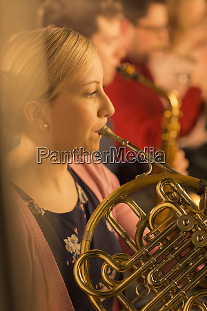 woman playing french horn in orchestra