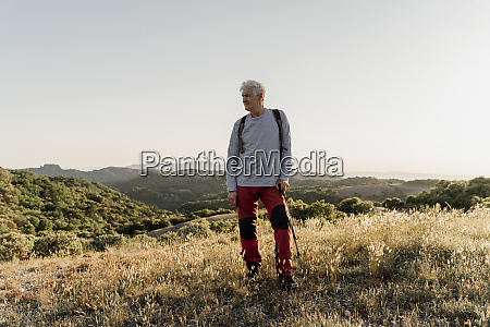 senior male hiker looking away while