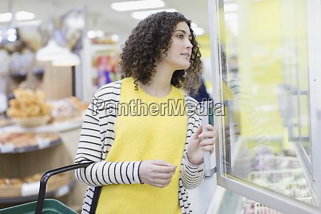 woman shopping frozen food in supermarket