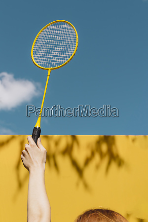 womans hand holding badminton racket over