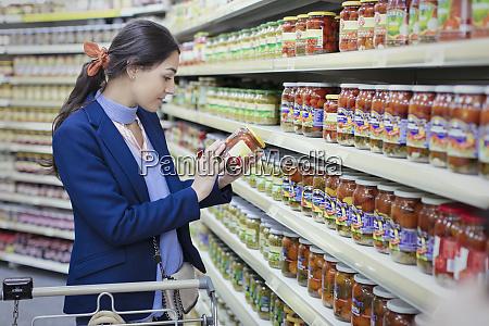 woman reading label on jar in
