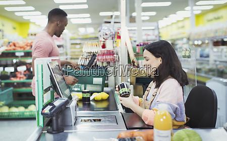 cashier helping customer at supermarket checkout