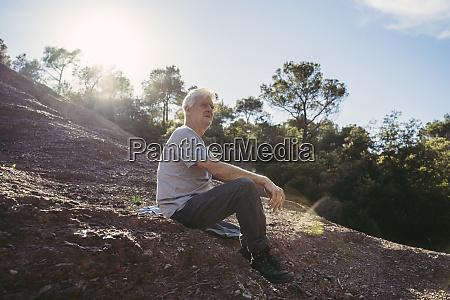 senior man sitting on ground during