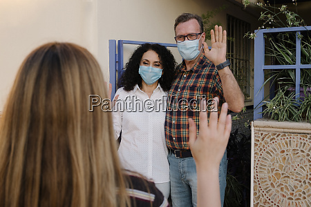 couple wearing masks waving hands to