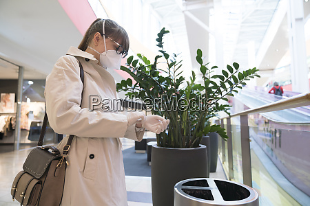 woman with face mask removing disposable