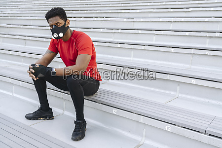 sportsman wearing face mask sitting on