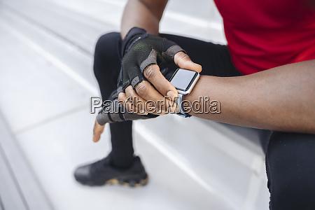 close up of sportsman wearing smartwatch