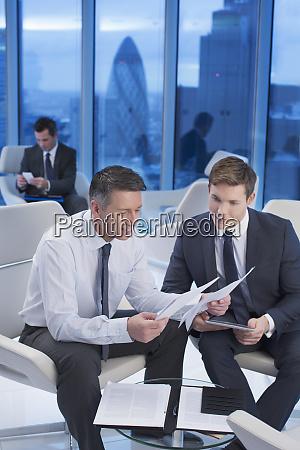 businessmen reviewing paperwork in office