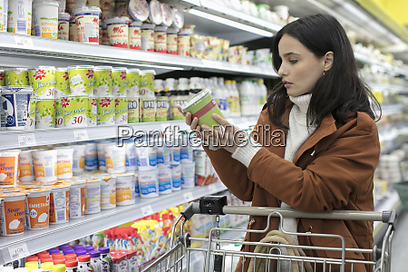 young woman reading label on container
