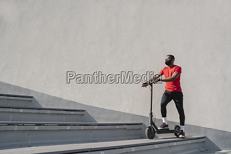 sportsman wearing face mask with scooter