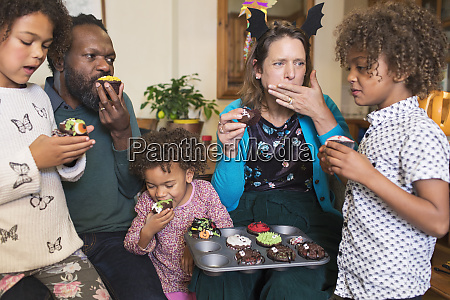 multiethnic family eating decorated halloween cupcakes