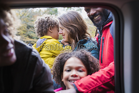 portrait happy family outside car window