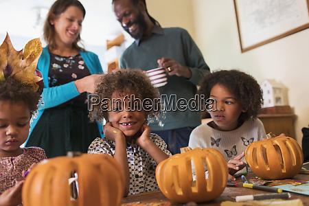 portrait happy boy carving pumpkins with
