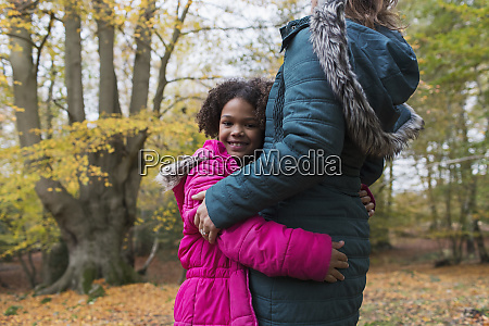 portrait of happy girl hugging mother