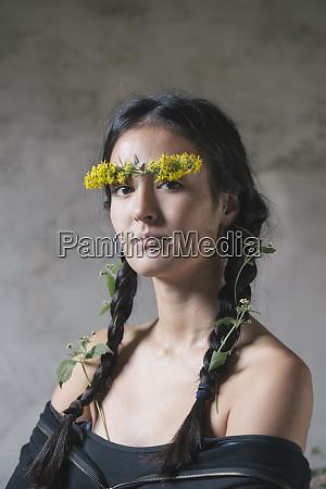 confident young woman with flower stuck
