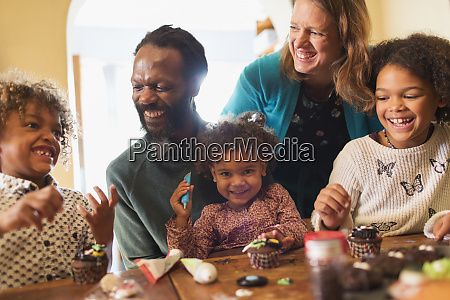 happy multiethnic family decorating cupcakes at