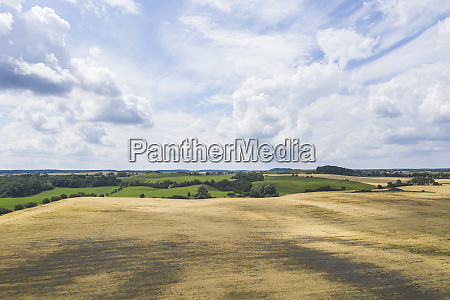 white clouds over countryside field in