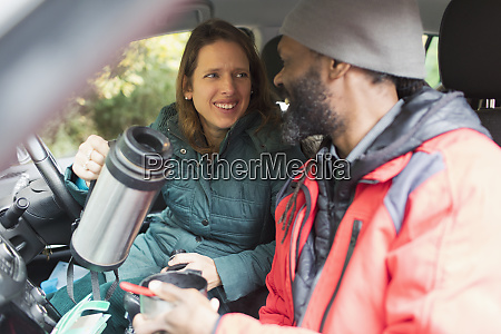 happy couple drinking coffee in car