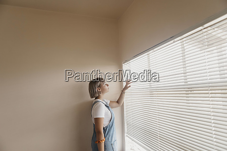 young woman looking through blinds at
