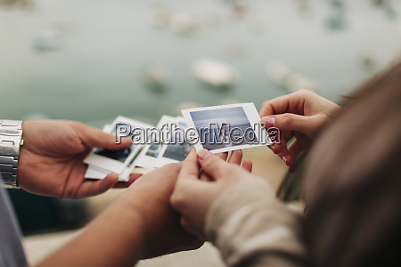 expectant couple watching photographs at harbor