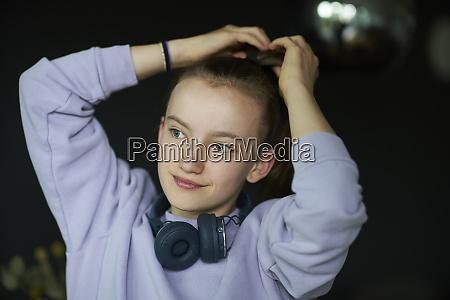 smiling girl tying ponytail while looking
