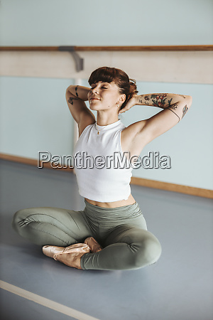 relaxed ballerina with hands behind head