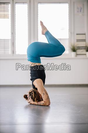 female ballerina performing headstand on floor