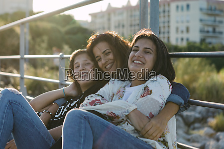 smiling mother with daughter sitting by