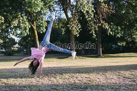 girl doing cartwheel on land against