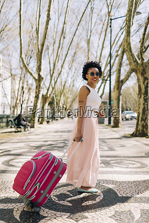 woman wearing sunglasses with suitcase standing