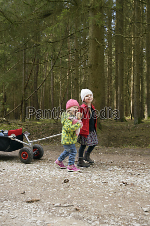 two little sisters pulling trolley on