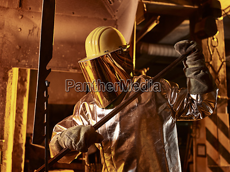 male worker holding metal rod in