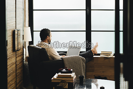 mature man sitting in armchair using