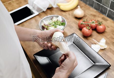 mature man standing in kitchen peeling