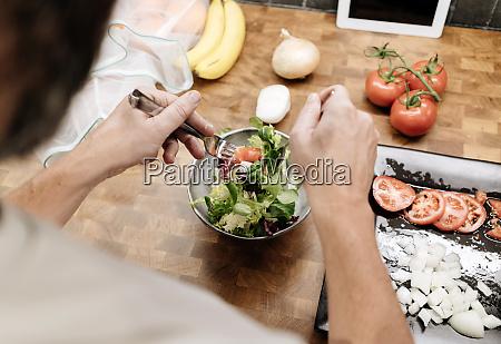 mature man standing in kitchen preparing