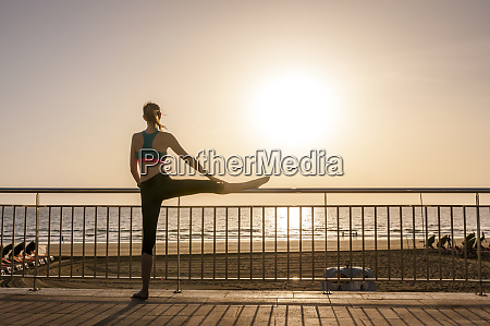 sporty woman stretching at the seafront