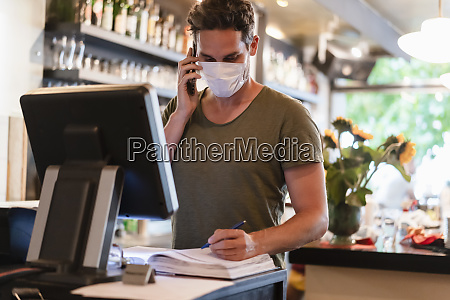 restaurant manager with protective mask using