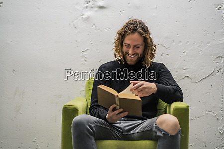 smiling young man reading book while